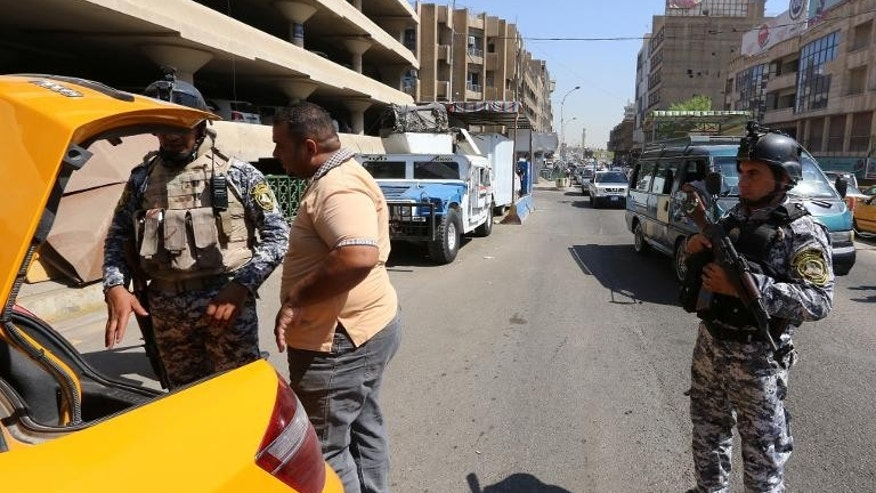 Iraqi security forces search a taxi cab at a mobile checkpoint in Baghdad on August 27, 2013. Car bombs mainly targeting Shiite-majority areas of Baghdad province killed at least 25 people and wounded more than 100 on Monday.