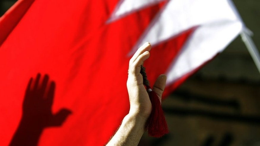 A Shiite protester waves a Bahrain flag during a rally in Manama, on March 22, 2011