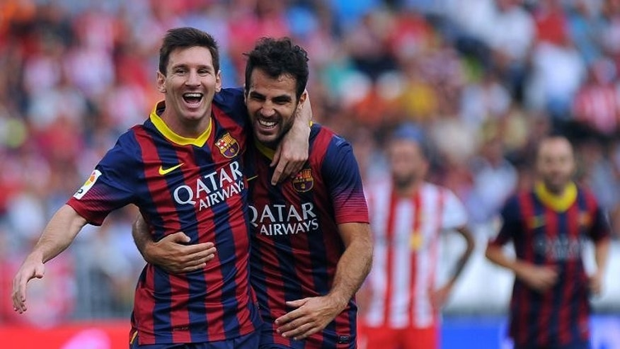 Barcelona's Lionel Messi (L) celebrates with Cesc Fabregas after scoring during the Spanish league match against UD Almeria in Almeria on September 28, 2013