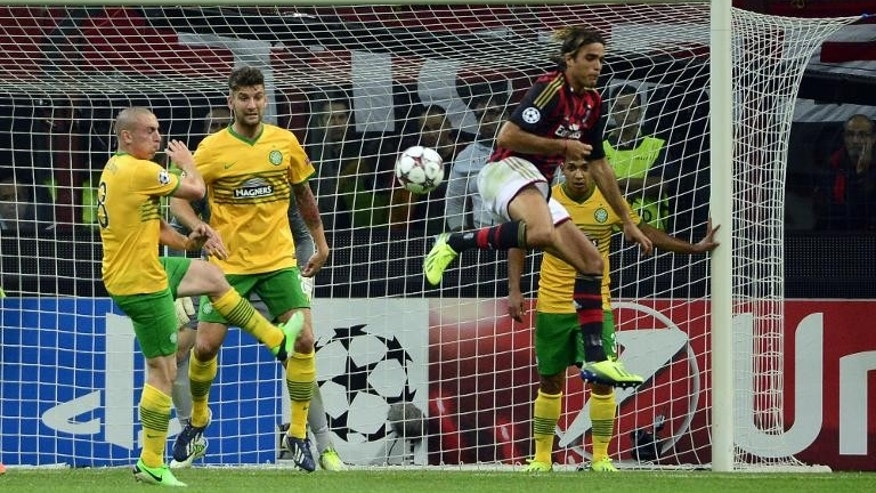 Celtic players fight off an attack by AC Milan's Alessandro Matri (R) during a match at the San Siro Stadium in Milan on September 18, 2013