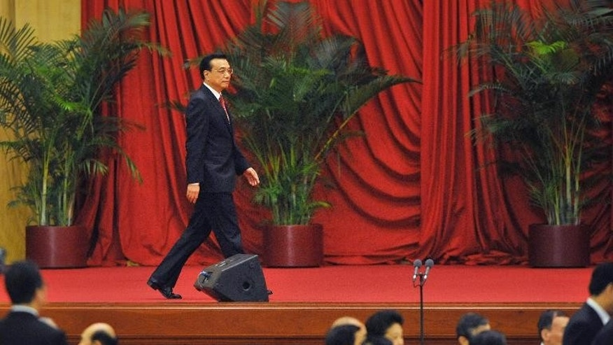 China's Premier Li Keqiang (C) walks along the stage before delivering a speech during the 64th National Day reception at the Great Hall of the People in Beijing on September 30, 2013