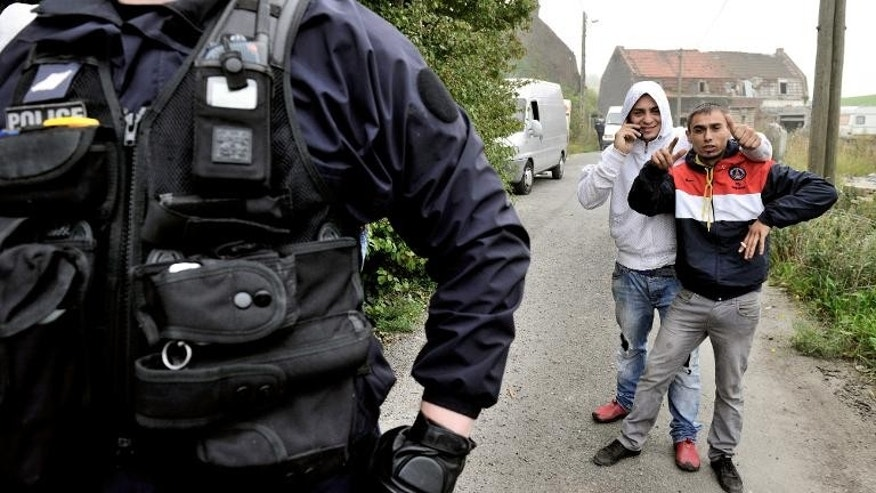 French police stand guard as Roma youths pose for pictures in the northern city of Wattrelos, on September 27, 2013