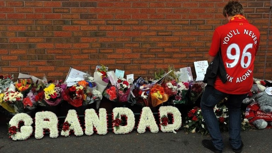 A supporter pays his respects outside Anfield to the 96 supporters who died in the 1989 Hillsborough disaster, at Anfield in Liverpool, north-west England on September 23, 2012