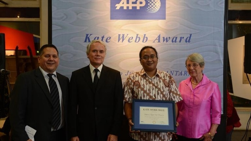 Indonesian journalist Stefanus Teguh Edi Pramono (2nd R) winner of the Agence France-Presse Kate Webb Prize, poses during a ceremony at the Antara Gallery in Jakarta on September 30, 2013