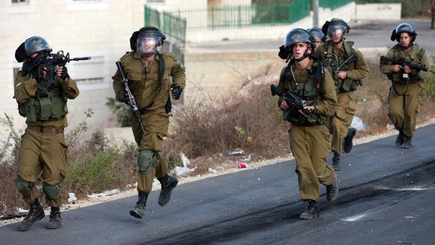 Israeli soldiers run during clashes with Palestinian protesters in Betunia on September 27, 2013