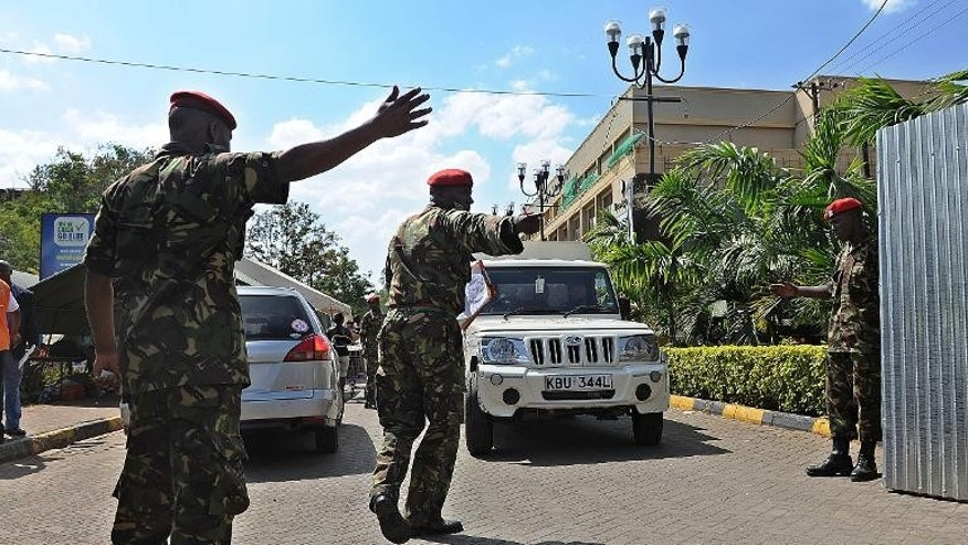 Military officers direct traffic on September 30, 2013 from the wreckage of the Westgate mall in Nairobi