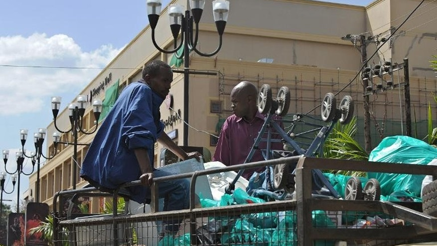Workers carry away salvaged goods on September 30, 2013 from wrecked shops at the Westgate mall in Nairobi