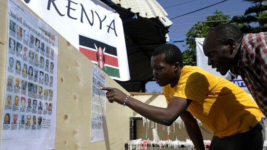 Kenyan men look at the list of the victims who were killed in the Westgate Mall massacre in Nairobi, on September 30, 2013