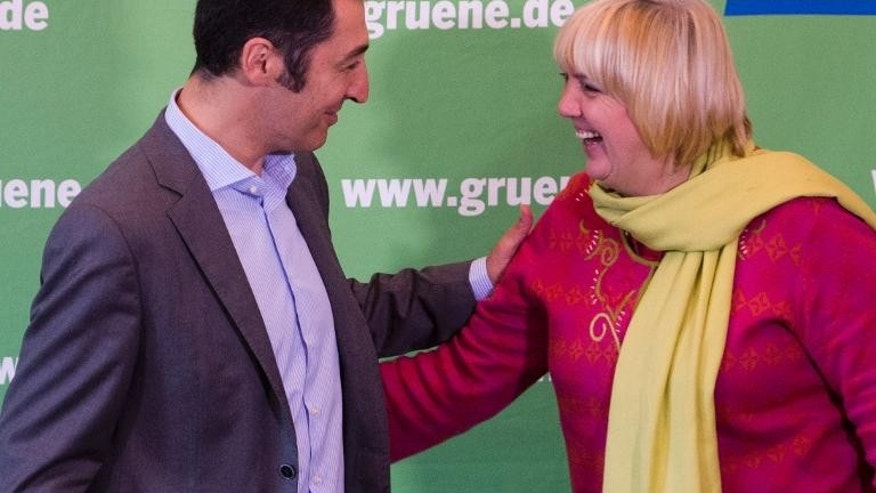 Green Party co-leaders Cem Oezdemir (left) and Claudia Roth greet each other in Berlin, on September 30, 2013