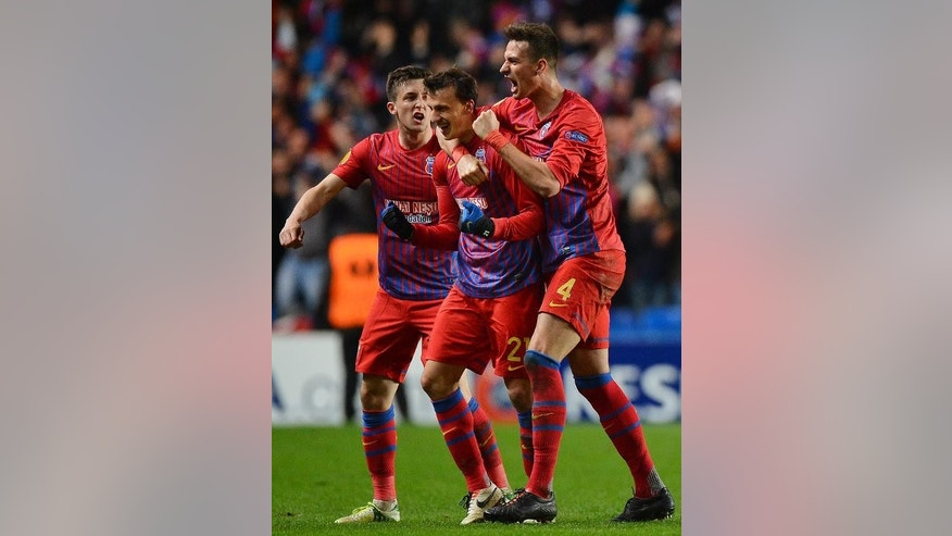 Steaua Bucurest's Vlad Chiriches (C) celebrates after scoring a goal during the Europa League match against Chelsea in London on March 14, 2013