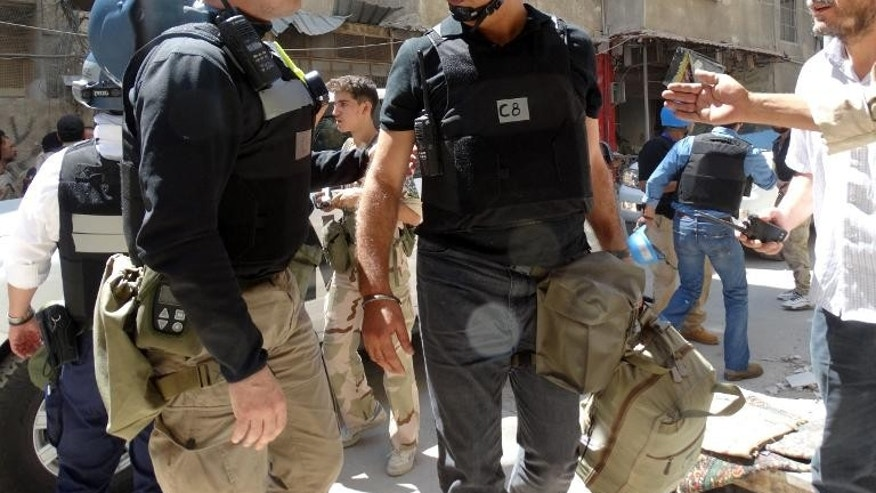 United Nations weapons experts arrive to inspect the site of a suspected chemical weapons strike in Damascus' eastern Ghouta suburb on August 28, 2013