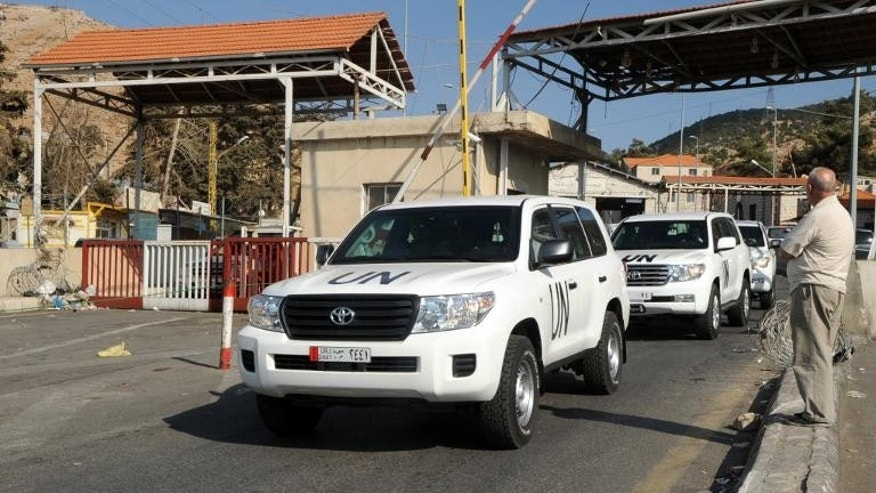A convoy of UN vehicles carrying a team of experts at the Lebanon-Syria border following their arrival on September 30, 2013