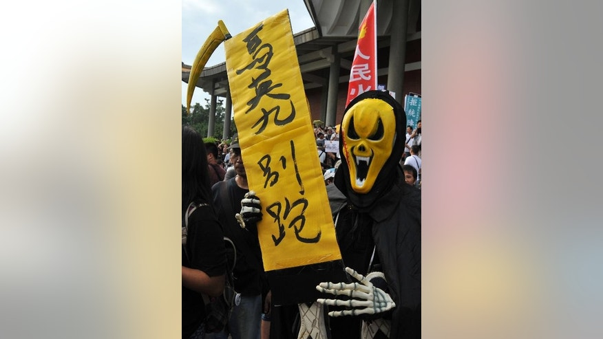 "A Taiwanese demonstrator wears a mask and holds a sign reading ""Down with Ma Ying-jeou"" during a rally in Taipei, on September 29, 2013"