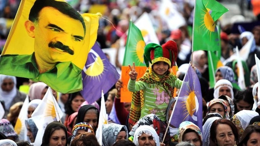 A child flashes a victory sign while demonstrators waves flag and a picture of jailed Kurdish leader Abdullah Ocalan during a rally at the Sisli district of Istanbul, on September 22, 2013