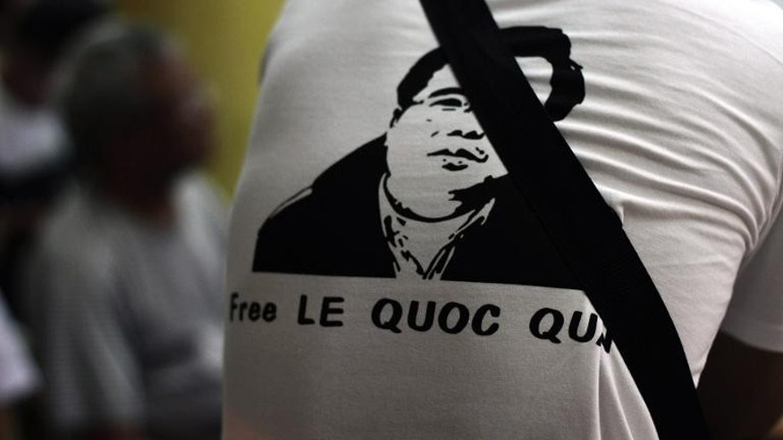 A man wearing a T-shirt displaying a portrait of democracy activist Le Quoc Quan is pictured during a mass in support of Quan at a catholic church in Vietnam on July 7, 2013