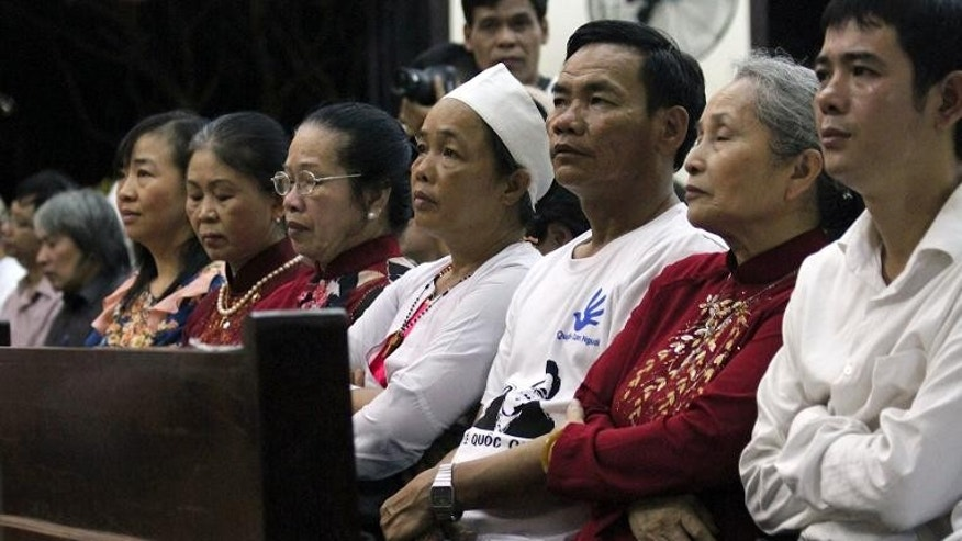 Image taken on July 7, 2013 shows Le Quoc Quyet (R), younger brother of democracy activist Le Quoc Quan, during a mass at a Catholic church in Vietnam