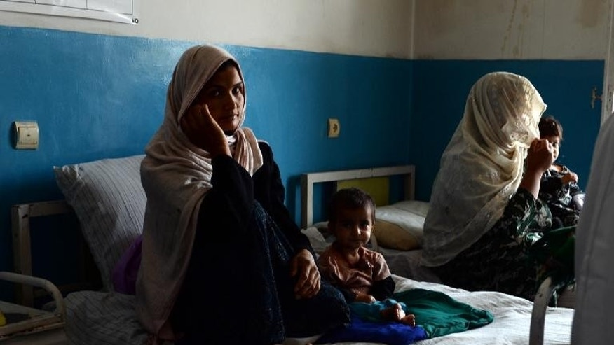 Afghan women and children wait to visit a doctor in Maidan Shar hospital in Wardak province on September 23, 2013