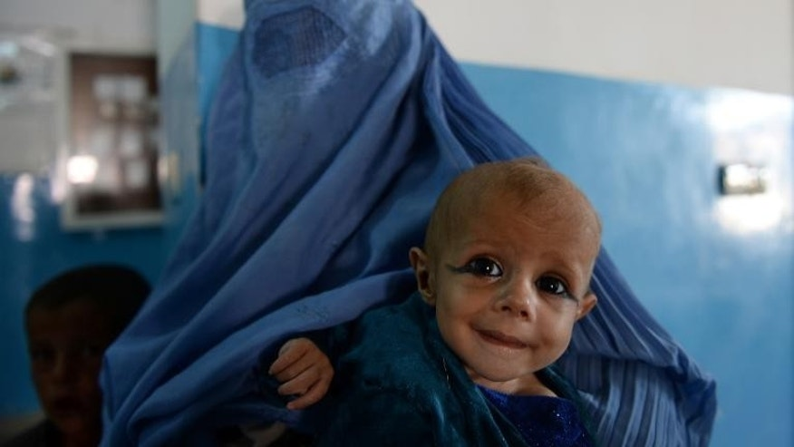 An Afghan woman holds her child as she waits to visit a doctor in Maidan Shar hospital in Wardak province on September 23, 2013