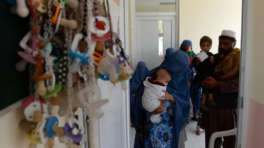 Afghan men and women hold their children as they wait to visit a doctor in Maidan Shar hospital in Wardak province on September 23, 2013