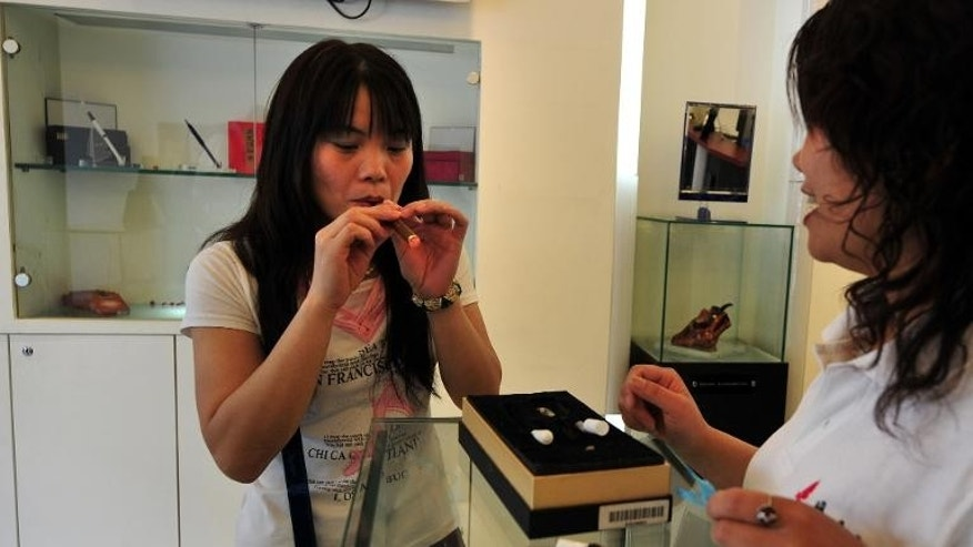 A customer is assisted by a salesperson at a shop selling electric smoking products in Beiijng in 2009 designed by Hon Lik