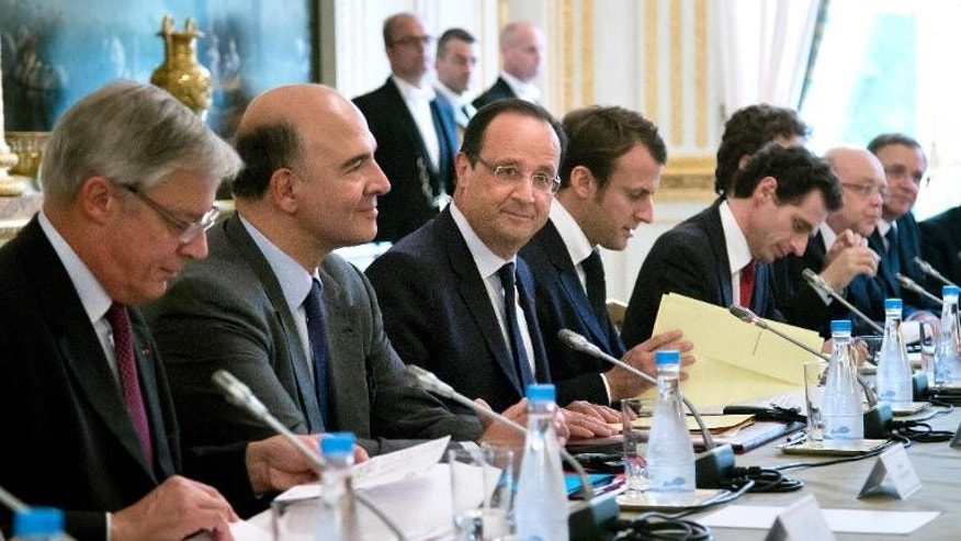 French President Francois Hollande (C) and French Finance Minister Pierre Moscovici (2nd L) attend a meeting with the Board of Governors of the European Central Bank, on October 1, 2013, at the Elysee presidential palace in Paris