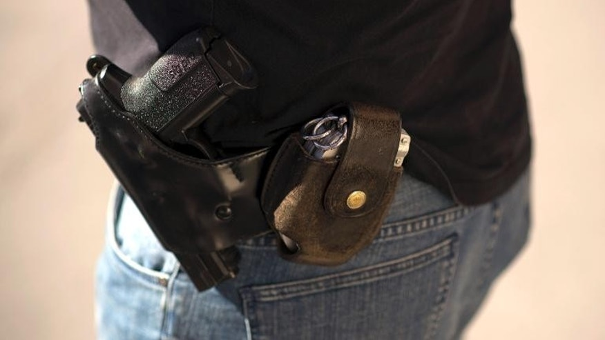 A SIG-Sauer Pro gun and handcuffs carried by a French policeman in Persan, outside Paris, on September 5, 2013