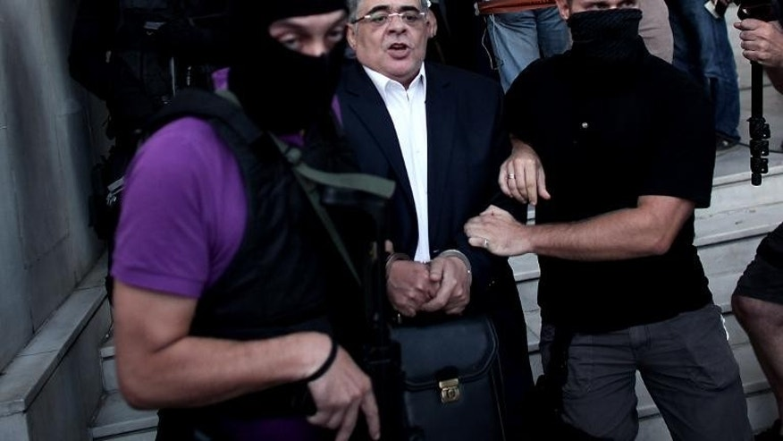 The leader of ultra-right wing Golden Dawn party Nikos Michaloliakos is escorted by masked police officers to the prosecutor's office from police headquarters in Athens on September 28, 2013