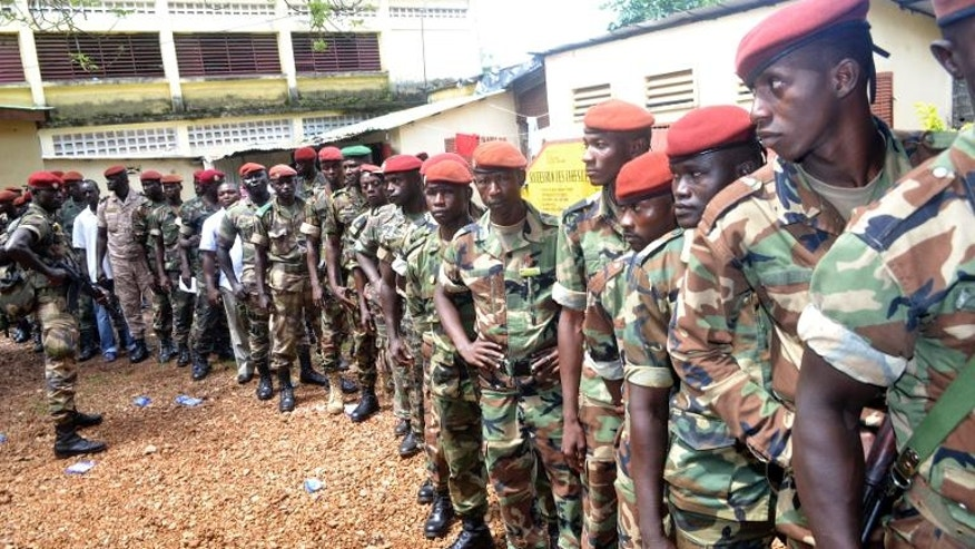 Guinean soldiers queue to vote at a polling station in Conakry on September 28, 2013