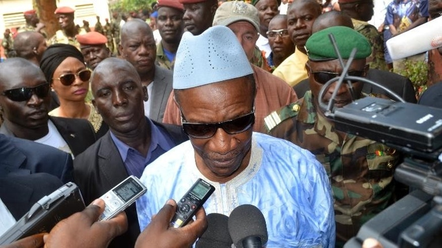 Guinean President Alpha Conde speaks to the press after casting his vote at a polling station in Conakry on September 28, 2013