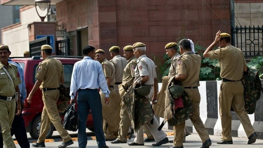 Indian police personnell carry riot gear at the Saket court complex in New Delhi on September 13, 2013