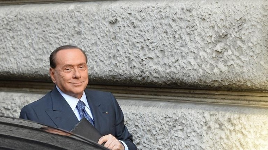 Italy's former Prime Minister Silvio Berlusconi smiles as he arrives for a meeting at the Italian Deputy Chamber on September 30, 2013 in Rome