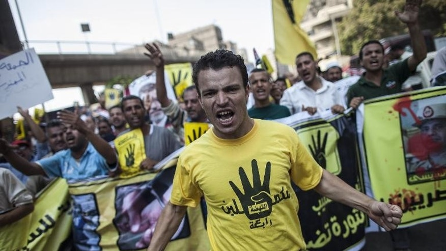 Members of the Muslim Brotherhood and supporters of ousted President Mohamed Morsi march through Cairo on September 6, 2013, wearing the hand logo recently adopted by the group