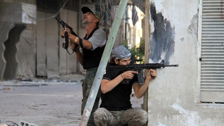Rebel fighters hold a position on a front line in the Damascus suburb of Yalda on September 18, 2013