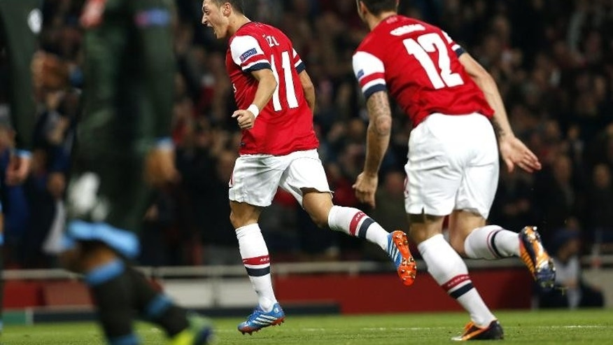 Arsenal's German midfielder Mesut Ozil (L) celebrates scoring the opening goal against SSC Napoli at the Emirates Stadium, North London, on October 1, 2013