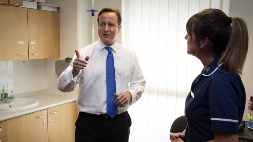 Prime Minister David Cameron talks with Sister Julie Lees during a visit to the Range Medical Centre in Whalley Range, Manchester, on October 1, 2013