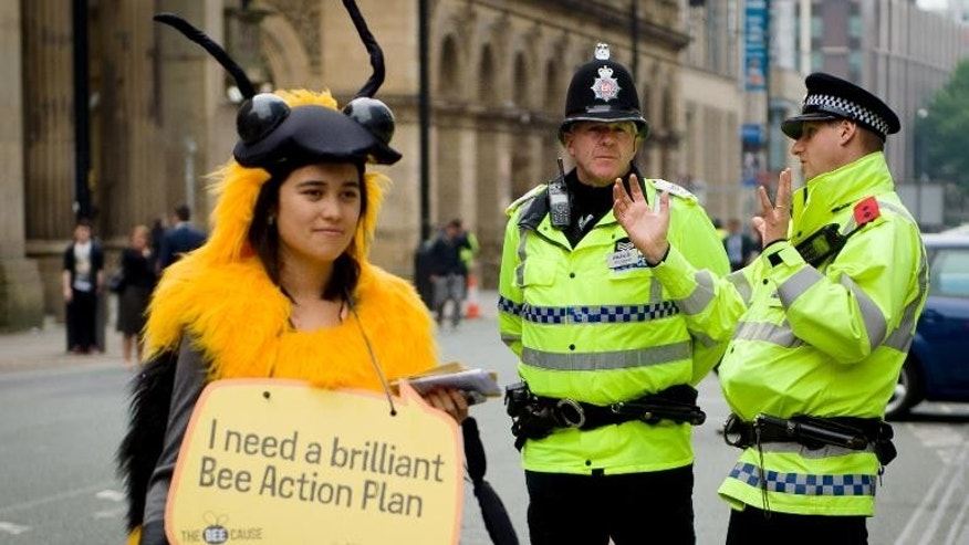 A woman demonstrating for the protection of the bee population stands next to two police officers outside the annual Conservative Party Conference in Manchester, on October 1, 2013