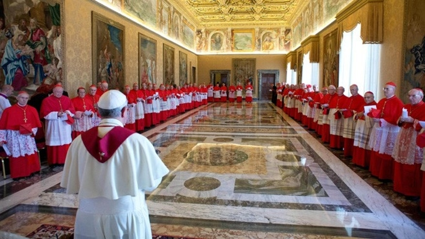 Sept. 30, 2013: In this picture provided by the Vatican newspaper L'Osservatore Romano, Pope Francis stands with cardinals during a consistory at the Vatican.