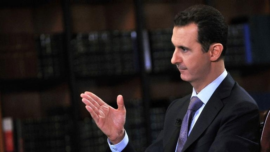 A handout picture released by SANA on September 29, 2013 shows President Bashar al-Assad gesturing during an interview with Italian television station Rai News 24 in Damascus