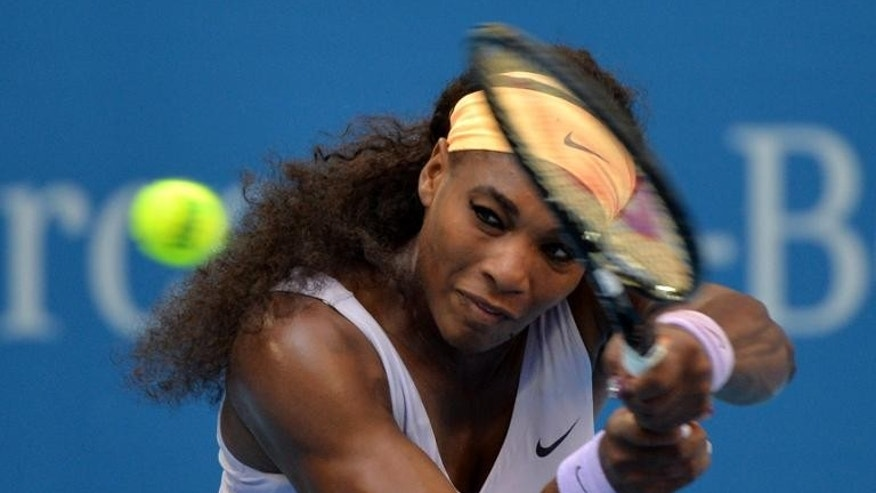 Serena Williams of the United States hits a return against Italy's Francesca Schiavone during their women's singles match at the China Open tennis tournament in Beijing, on October 1, 2013. Williams won 6-4, 7-5