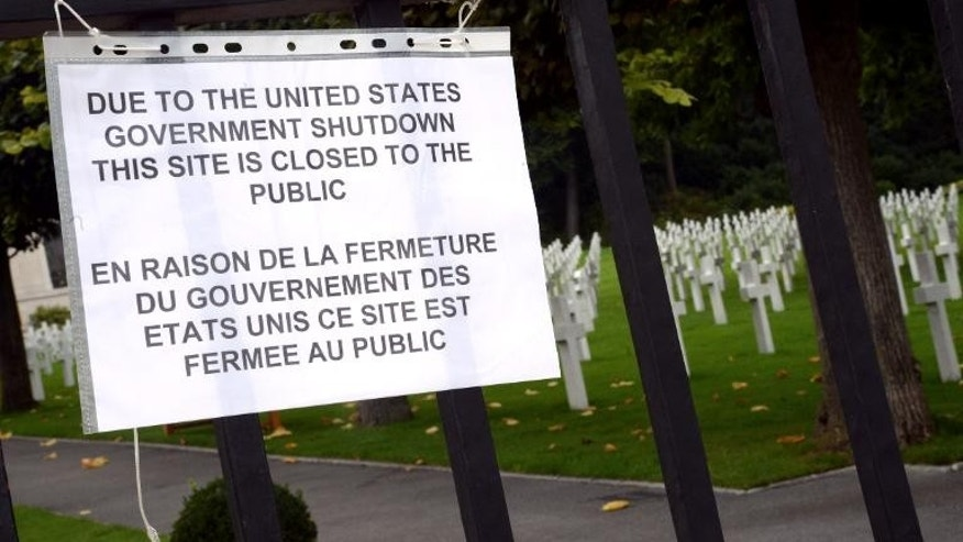 A board informs visitors of the closing of the Suresnes American Cemetery and Memorial, west of Paris, on October 1, 2013, after US Congress was unable to agree on a federal budget and shut down for the first time in 17 years