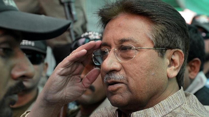 Former Pakistani president Pervez Musharraf (C) is escorted by soldiers as he salutes on his arrival at an anti-terrorism court in Islamabad in April 2013