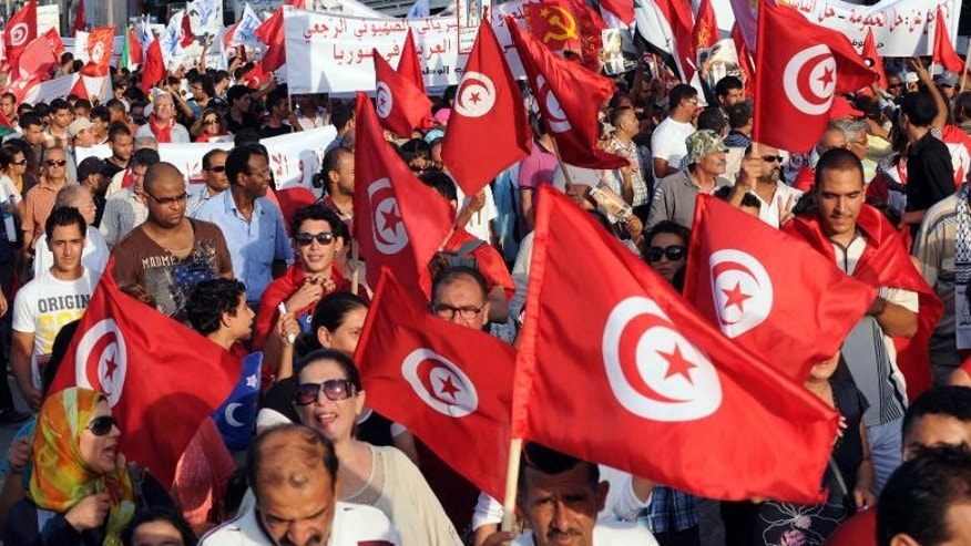 Tunisians wave their national flag as they march outside the National Assembly in Tunis on September 7, 2013