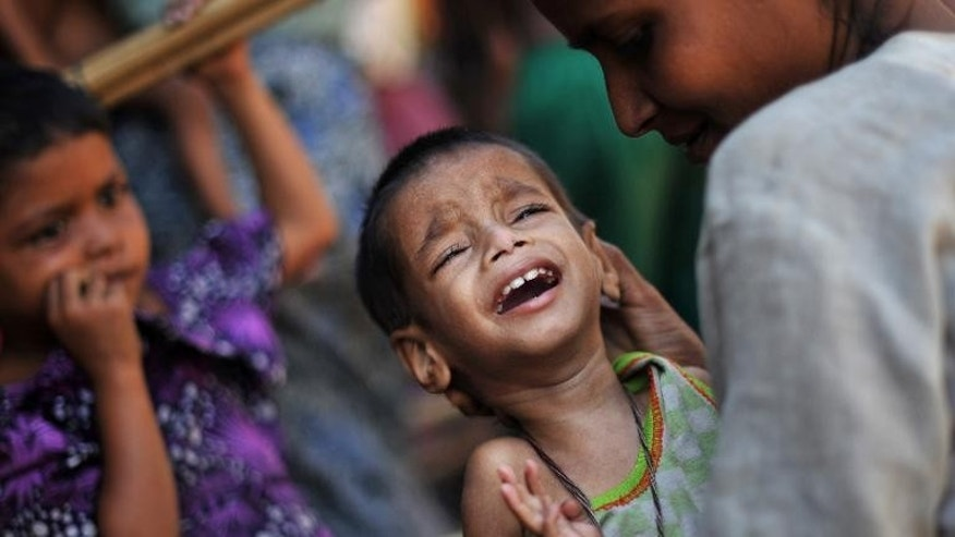 A Muslim Rohingya mother comforts her crying child as they wait for medical care at a clinic in the Bawdupha Internally Displaced Persons' camp on the outskirts of Sittwe, the capital of Myanmar's western Rakhine state, on November 2, 2012