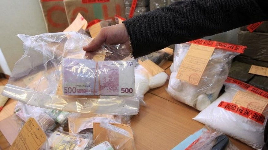 A police officer presents a bundle of cash sized with cocaine, heroin and cannabis on September 17, 2013 in Nice, France