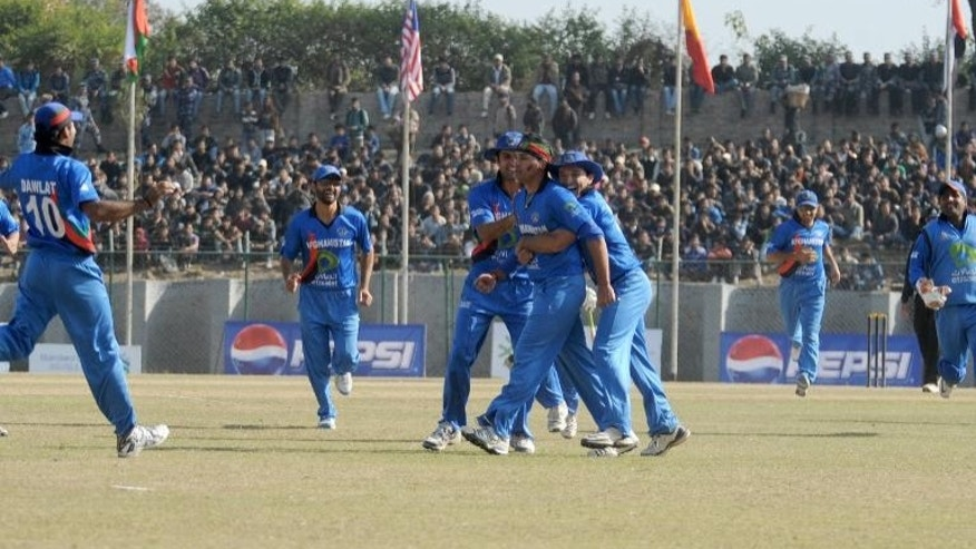 Afghani player Hamid Hassan (centre) celebrates with teammates after taking wicket of Hong Kong player Baber Hayat (unseen) during the Asian Cricket Council (ACC) Twenty20 cup final in Kathmandu on December 11, 2011
