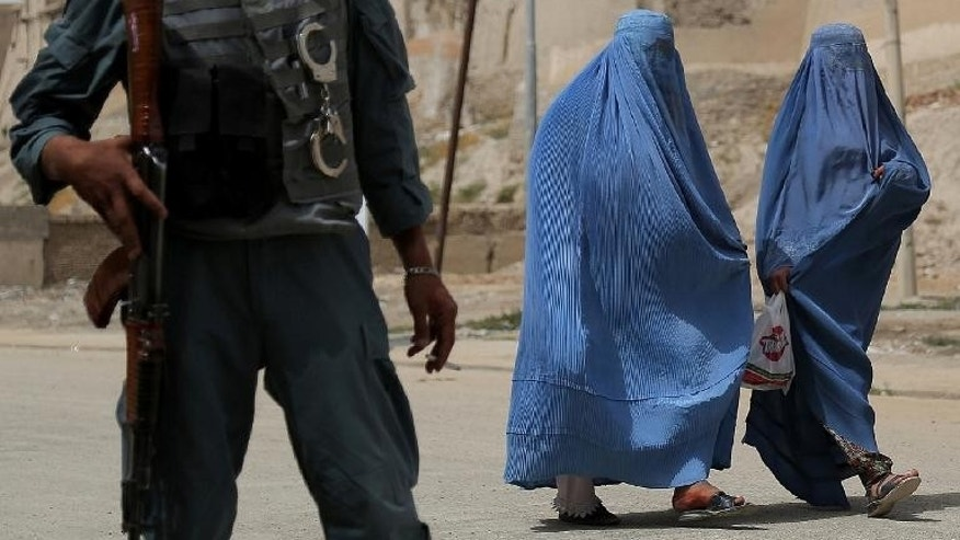 Two Afghan women walk past as a policeman stands guard in Ghazni, on August 15, 2013