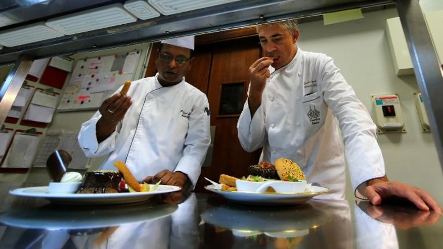 French chef Sandro Gamba (R) tastes a camel burger dish at a hotel in Abu Dhabi on September 16, 2013