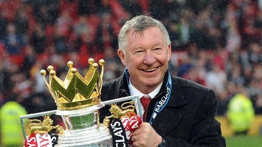 Then Manchester United manager Alex Ferguson holds the Premier League trophy after a match against Swansea City at Old Trafford in Manchester on May 12, 2013