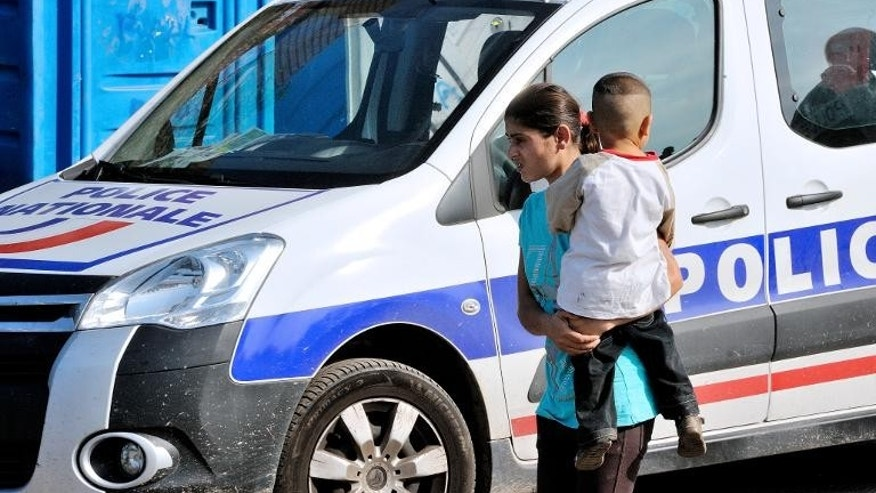 Roma children walk next to a French police car in Roubaix, northern France, on October 1, 2013