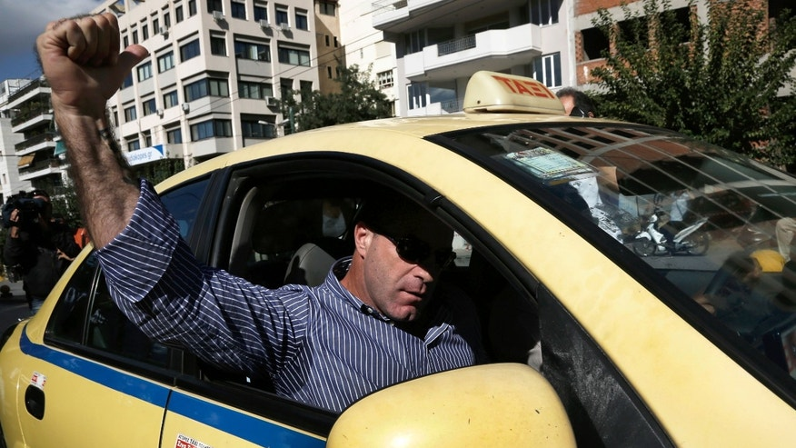 Lawmaker of the extreme far-right Golden Dawn party Nikos Michos celebrates raising his fist from a taxi window after a judicial authorities' decision to conditionally release him in Athens, Wednesday, Oct. 2, 2013. A Greek court released three lawmakers from Greece's extremist right-wing Golden Dawn party from custody pending trial, after they provided initial testimony in criminal investigation triggered by the slaying of a left-wing rapper. A fourth lawmaker, Ioannis Lagos, was jailed pending trial. (AP Photo/Fosphotos, Konstantinos Tsakalidis)